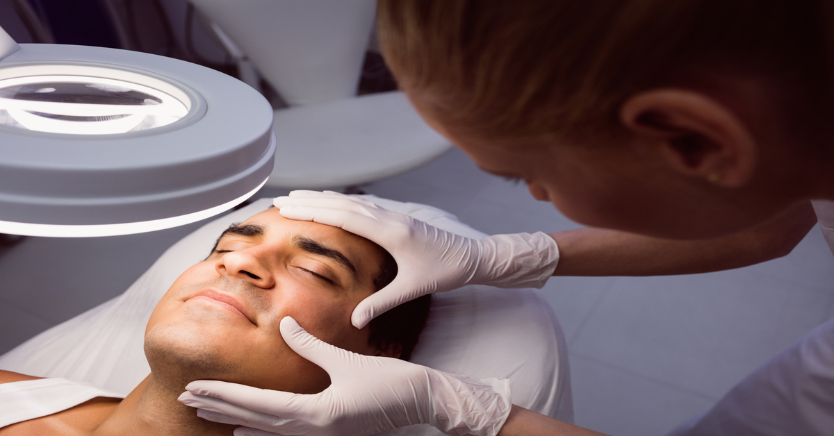Doctor examining mans face for cosmetic treatment at clinic